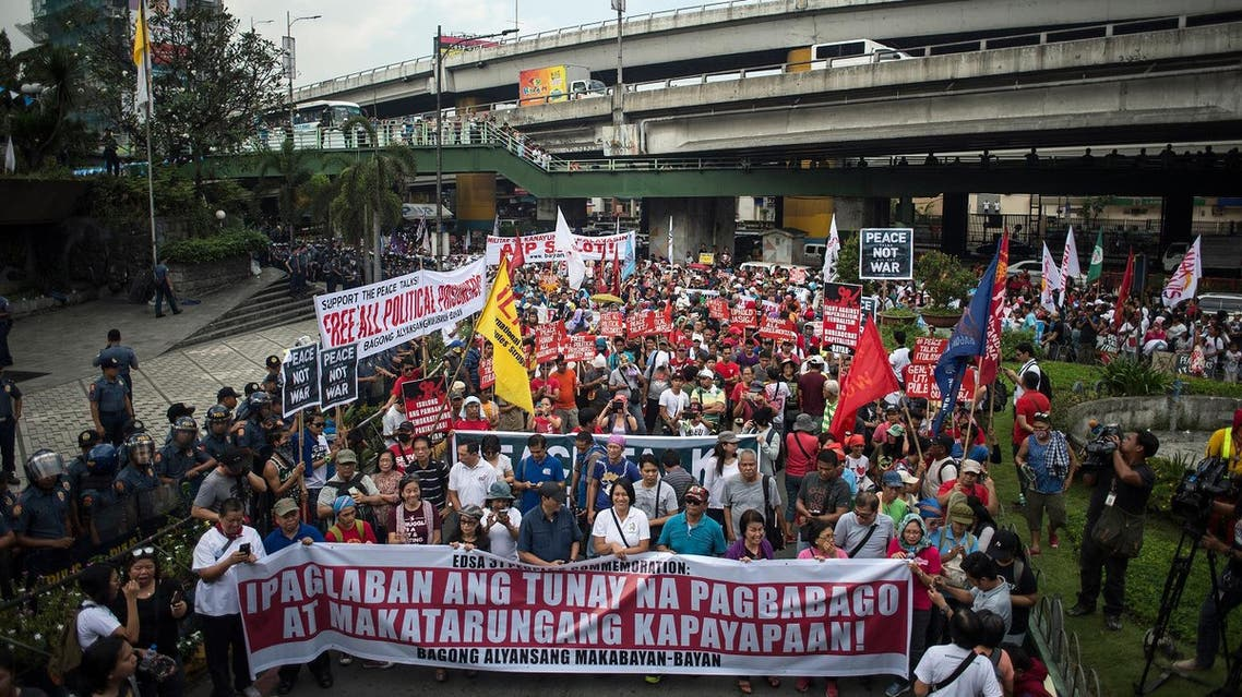 """Activists march on the EDSA highway on their way to protest in front of the Armed Forces of the Philippines (AFP) headquarters in Manila on February 25, 2017, during the 31st anniversary of the """"People Power"""" revolution. More than 1,000 people took to the streets of Manila on February 25 to protest Philippine President Rodrigo Duterte's brutal war on drugs, following the arrest of his most high-profile critic. (AFP)"""