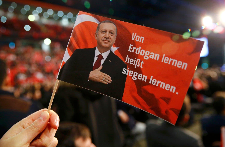 ایک شخص نے ترک صدر رجب طیب ایردوآن کی تصویر والا بینر اٹھا رکھا ہے۔