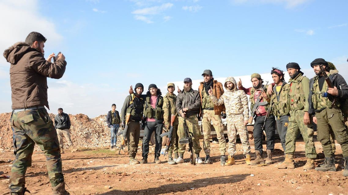 Fighters from the Free Syrian Army have their picture taken as they battle against ISIS militants near the town of Qabasin. (AFP)