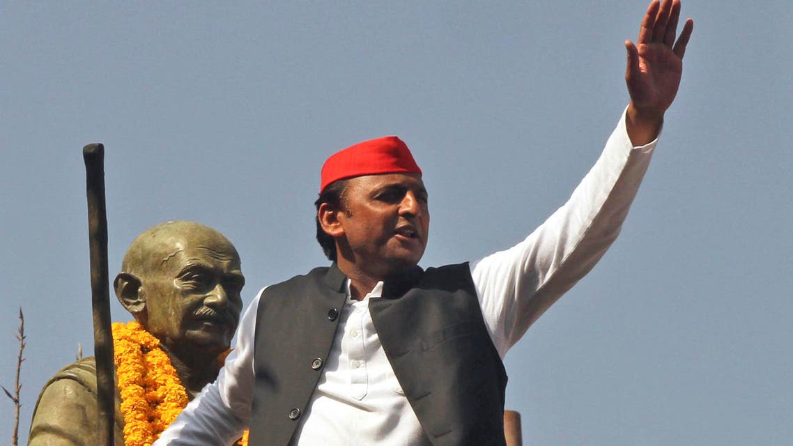 Uttar Pradesh state Chief Minister Akhilesh Yadav holds on to a statue of Mahatma Gandhi and waves to the crowd during an election campaign rally in Allahabad, India, on Feb. 21, 2017. (AP)