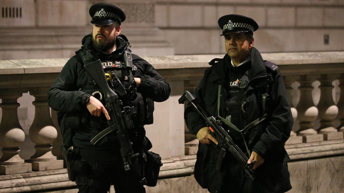 British police officers, some armed gather together ahead of the New Year's celebrations, in central London on December 31, 2016. London will have 3,000 officers on patrol with crowds flocking to line the banks of the Thames to watch the fireworks around the London Eye Ferris wheel.