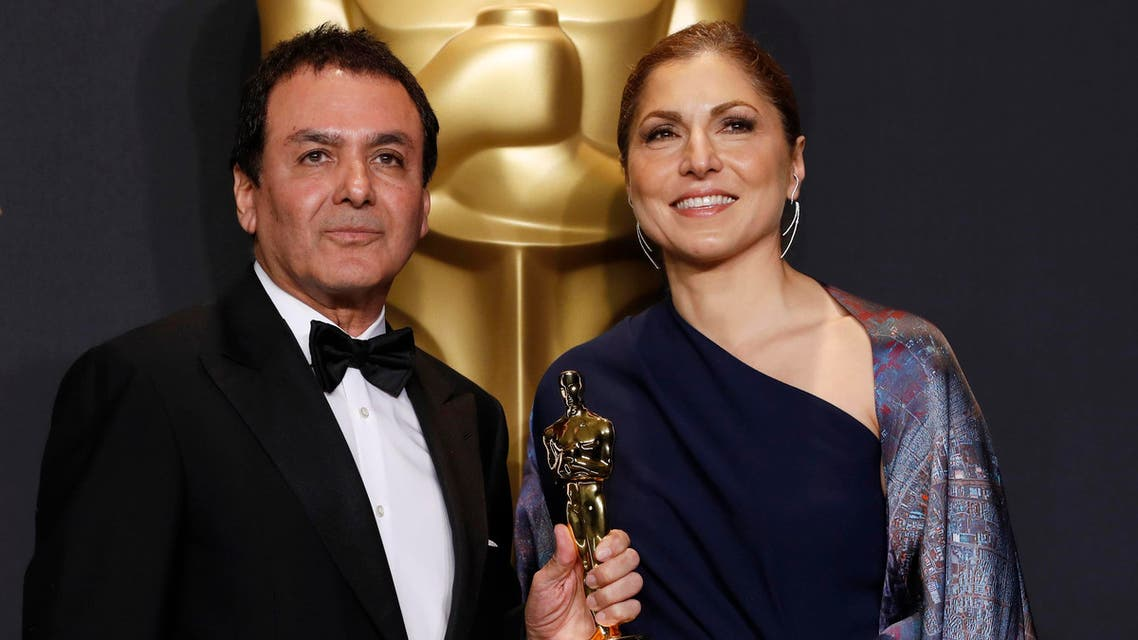 Anousheh Ansari and Firouz Naderi pose with the Oscar they accepted on behalf of Asghar Farhadi
