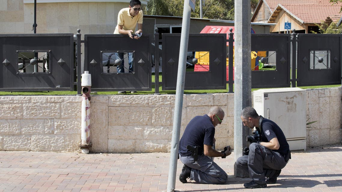 Israeli forensic policemen check the area after a rocket fired from the Gaza Strip hit in the southern Israeli town of Sderot, a few kms away from the Hamas-run Palestinian coastal territory, on October 5, 2016.