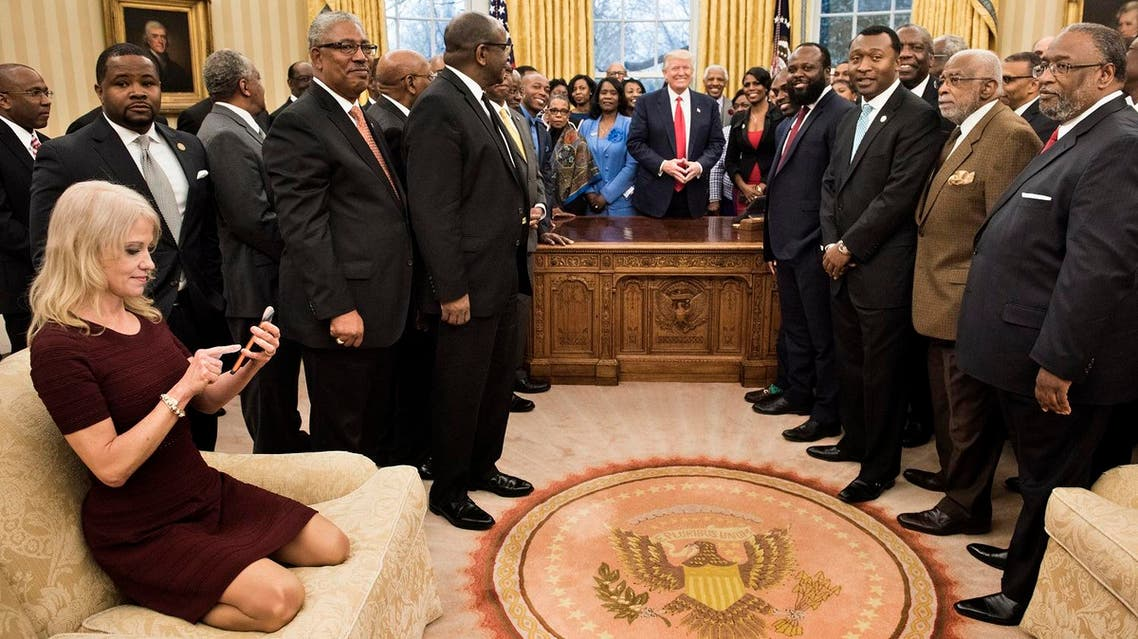 Counselor to the President Kellyanne Conway (L) checks her phone after taking a photo as US President Donald Trump and leaders of historically black universities and colleges pose for a group photo in the Oval Office of the White House before a meeting with US Vice President Mike Pence February 27, 2017 in Washington, DC. (AFP)