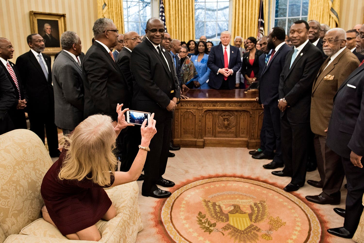Counselor to the President Kellyanne Conway takes a photo as US President Donald Trump and leaders of historically black universities and colleges talk before a group photo in the Oval Office of the White House before a meeting with US Vice President Mike Pence February 27, 2017 in Washington, DC. (AFP)