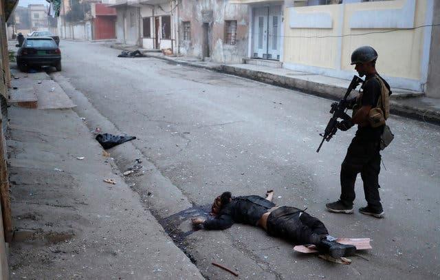 جندي عراقي يقف فوق جثة داعشي