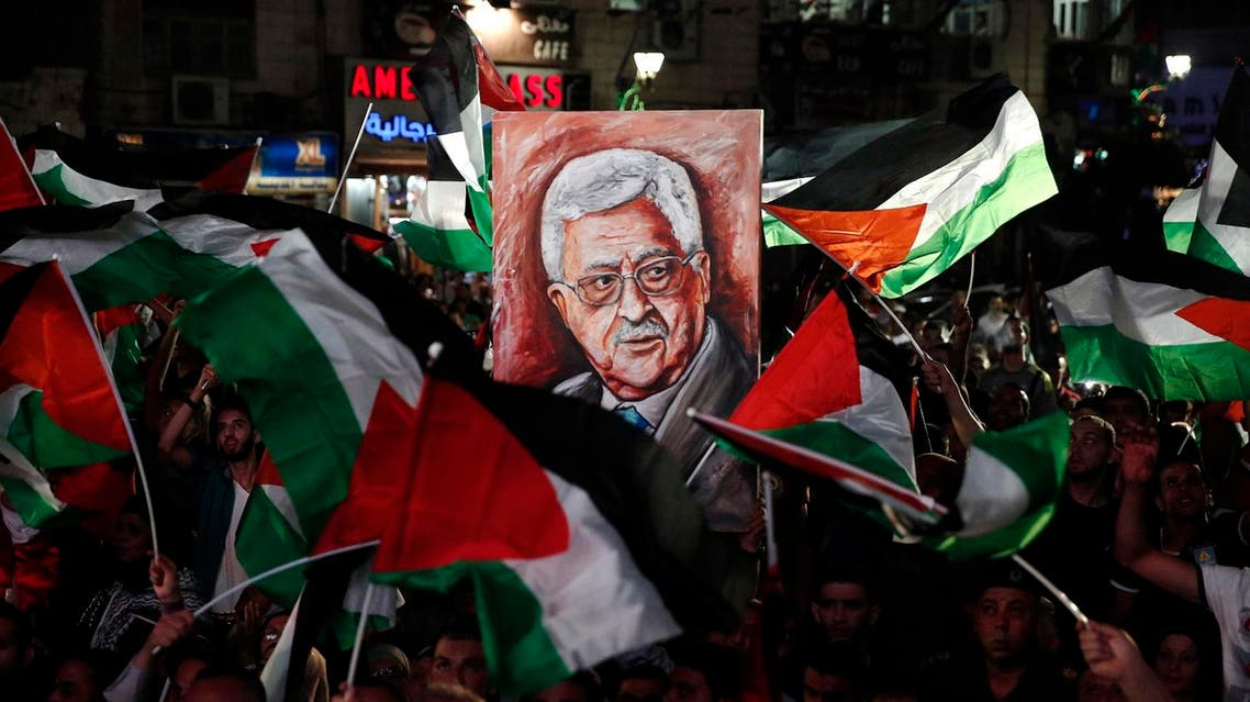 Palestinians wave their national flags and a portrait of their president Mahmud Abbas as they watch a live-screening of his speech followed by the raising of the Palestinian flag at the United Nations headquarters in New York, on September 30, 2015 in the city of Ramallah. Earlier in the week the UN General Assembly, by a two-thirds vote, adopted a resolution allowing the flags of Palestine and the Holy See -- both of which have non-member observer status -- to be hoisted alongside those of member states. AFP