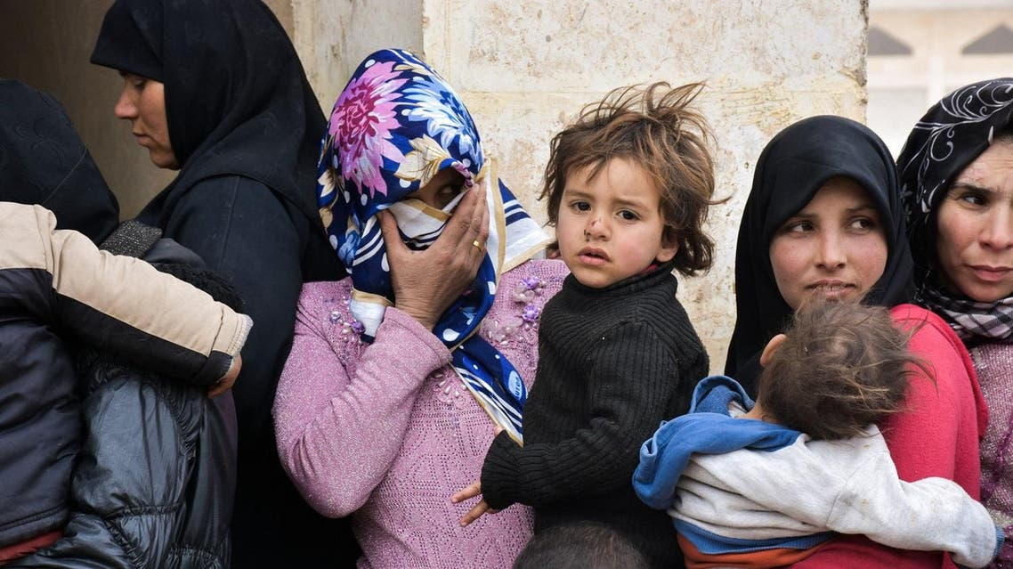 Displaced Syrian women queue up to receive medical aid and vaccines from Russian Army forces through paediatric field hospitals in the district of Jibreen, on the outskirts of the northern Syrian city of Aleppo on March 1, 2017. AFP