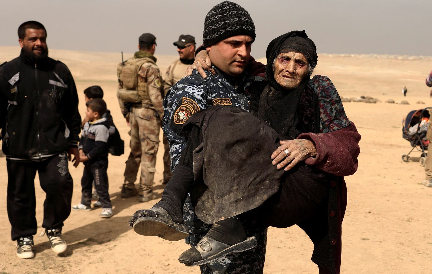 Khatla Ali Abdullah, 90, a displaced Iraqi women who fled her home, is carried by a member of the Iraqi forces in the desert in western Mosul, Iraq February 27, 2017. REUTERS