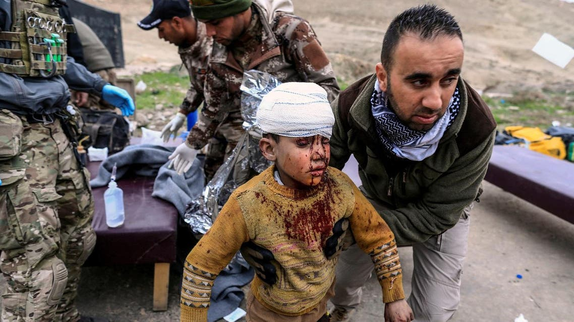 A boy injured in a mortar attack walks toward an ambulance after being treated by medics in a field clinic as Iraqi forces battle with ISIS militants, in western Mosul. (Reuters)