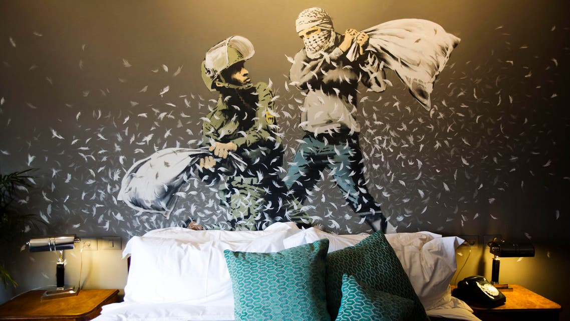 "A Banksy wall painting showing Israeli border policeman and Palestinian in a pillow fight is seen in one of the rooms of the ""The Walled Off Hotel"" in the West Bank city of Bethlehem, Friday, March 3, 2017. (AP)"