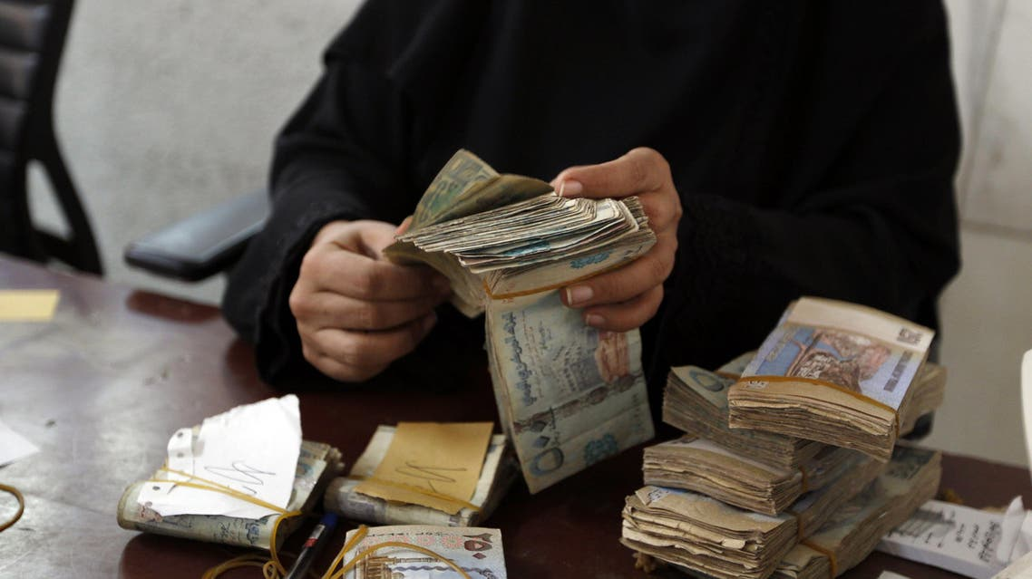 An employee counts stacks of Yemeni currency at the Central Bank of Yemen in the capital Sanaa on August 25, 2016.