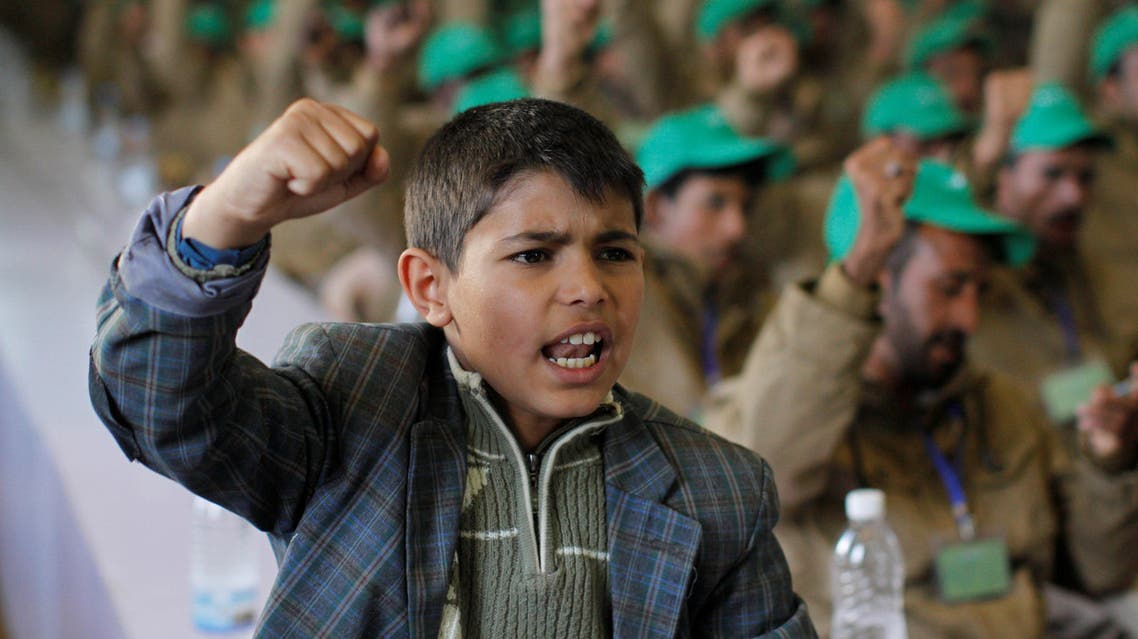 A boy shouts slogans next to pro-Houthi fighters, who have been injured during recent fighting, during a rally held to honour those injured or maimed while fighting in Houthi ranks in Sanaa, Yemen January 29, 2017. reuters