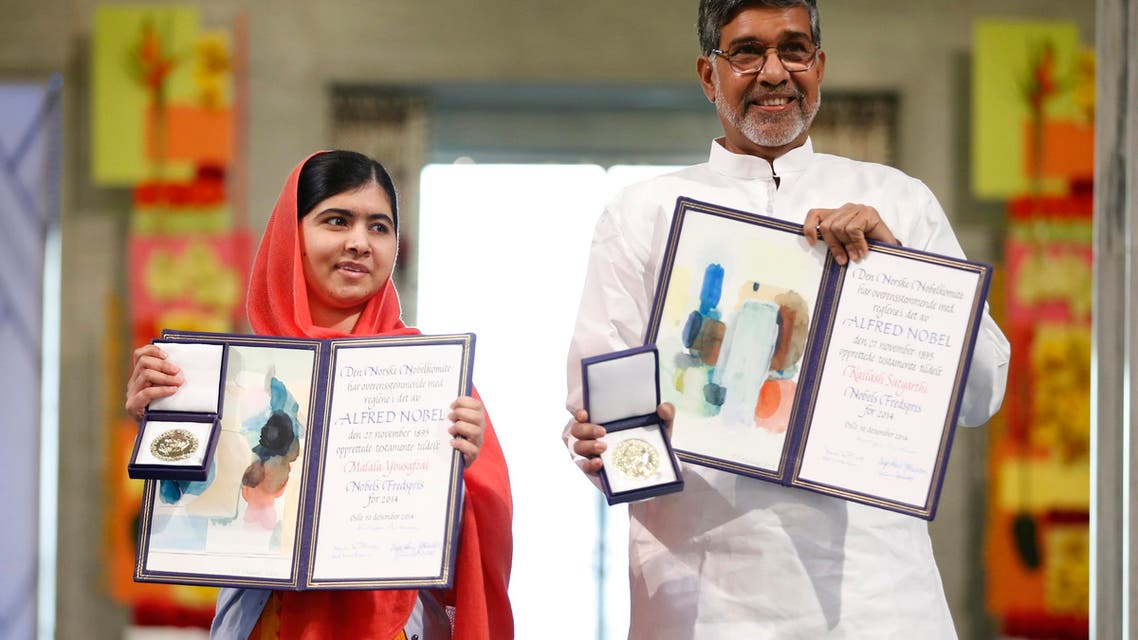 Nobel Peace Prize laureates Kailash Satyarthi (R) and Malala Yousafzai display their medals and diplomas during the Nobel Peace Prize awards ceremony at the City Hall in Oslo, Norway, on December 10, 2014