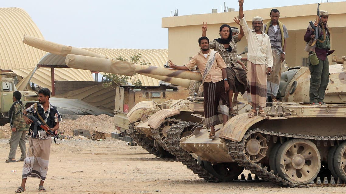 Members of a coalition of fighters made up of local tribes, Popular Resistance Committees and supporters of the southern Yemeni separatist movement, who are all opposing the Shiite-Huthi movement, flash the sign for victory as they stand on a tank at the Al-Anad airbase, in Yemen's southern Lahj governorate, north of Aden, on March 24, 2015.