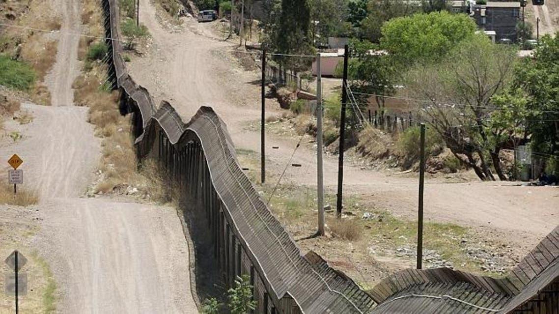 قطاع من الحدود بين المكسيك وأميركا، والسيارة دورية أميركية تراقب المنطقة