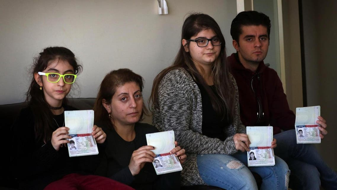 Fuad Sharif Suleman and his family show their US immigrant visas in Arbil, the capital of the Kurdish autonomous region in northern Iraq, on January 30, 2017 after returning to Iraq from Egypt, where they were prevented from boarding a plane to the US. (AFP)