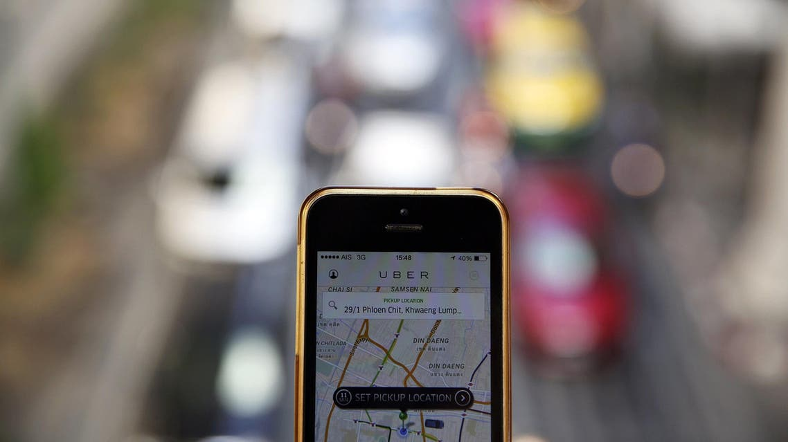 A phone running the Uber application is held above the traffic in central Bangkok December 10, 2014. (Reuters)