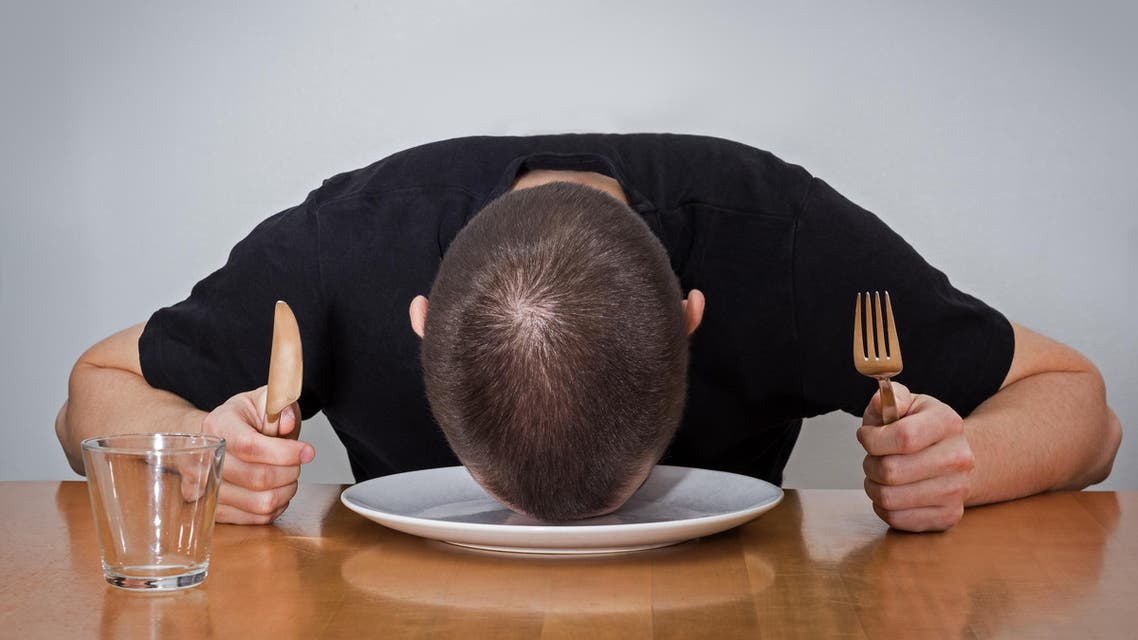 Man sleeping on a plate, tired of waiting for food