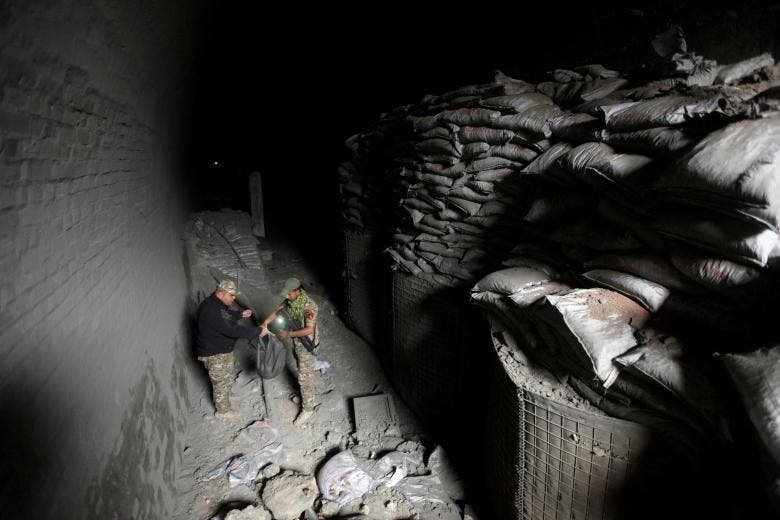Members of the rapid response forces inspect a tunnel was used by ISIS militants as an underground training camp in the hillside overlooking Mosul, Iraq. (Reuters)