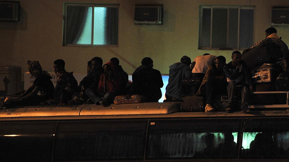 Illegal migrants sit on the roof of a police bus with their belongings on November 13, 2013 (File Photo: Fayez Nureldine/AFP)