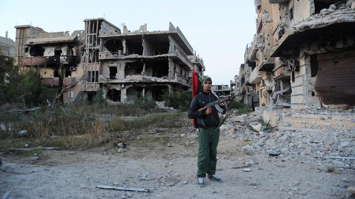 A civilian fighter holding the Libyan flag stands in front of damaged buildings in Benghazi, Libya (File Photo: AP/Mohammed el-Shaiky)