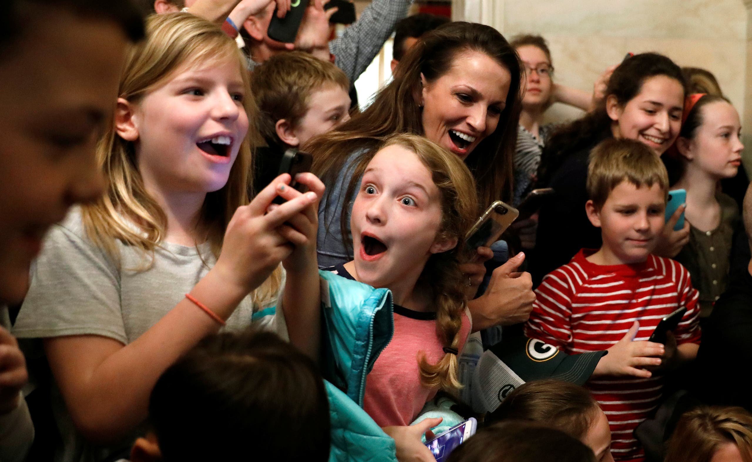 A young girl reacts after U.S. President Donald Trump made a surprise appearance in front of her White House tour group in Washington, U.S. March 7, 2017