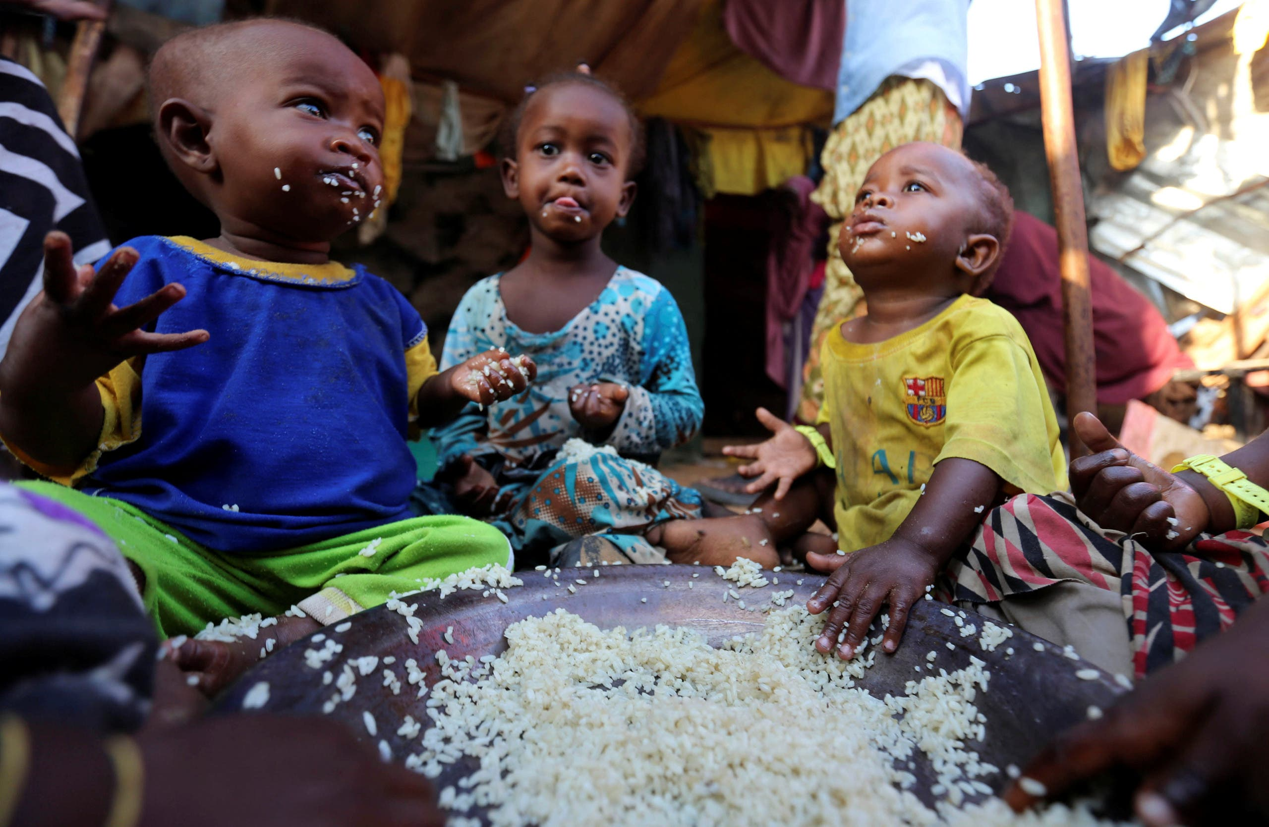 Internally displaced Somali children eat boiled rice outside their family's makeshift shelter at the Al-cadaala camp in Somalia's capital Mogadishu March 6, 2017