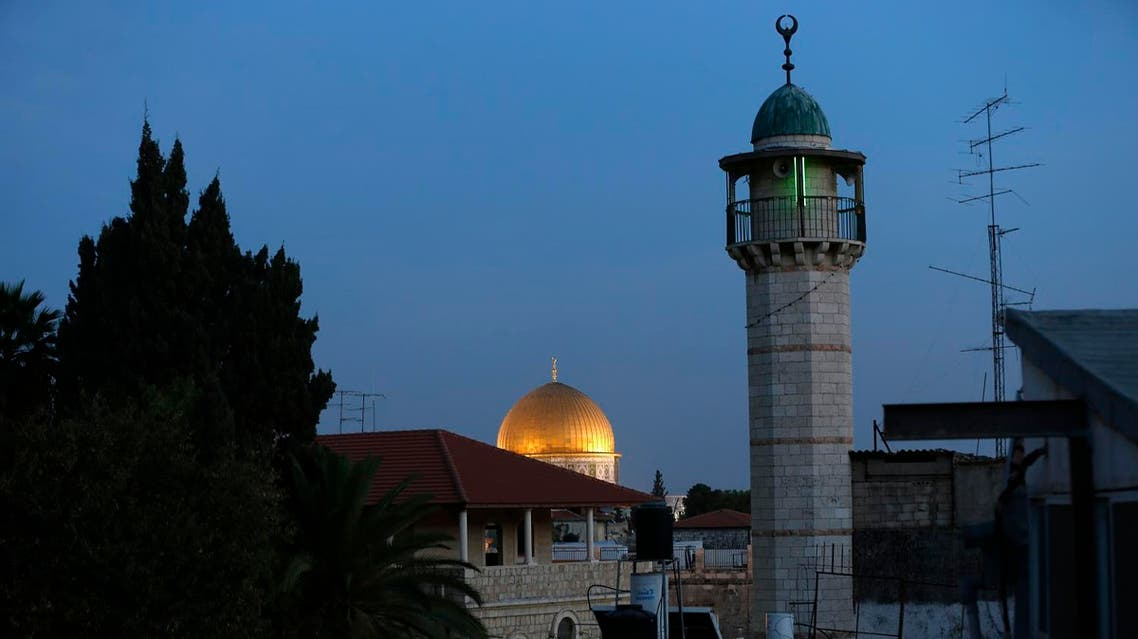 A picture taken on November 21, 2016 shows the minaret (R) of a mosque and the Dome of the Rock (background) in a Palestinian neighbourhood of east Jerusalem's Old City, on November 21, 2016. (AFP)