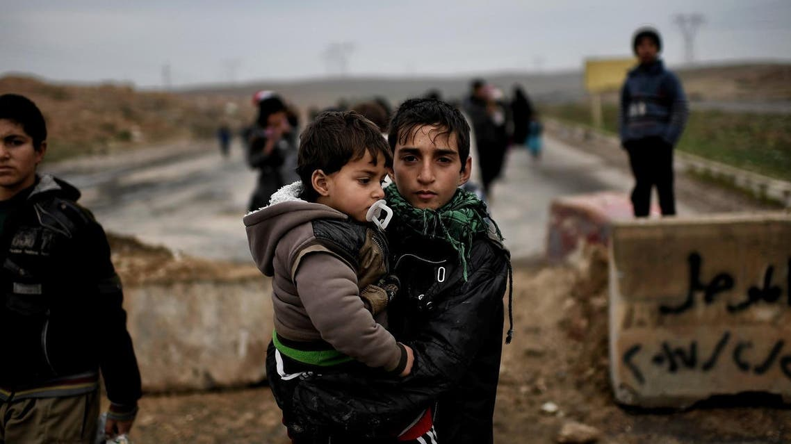 Iraqi families walk down a road as they flee Mosul on March 3, 2017, during an offensive by security forces to retake the western parts of the city from Islamic State (IS) group fighters.  ARIS MESSINIS / AFP