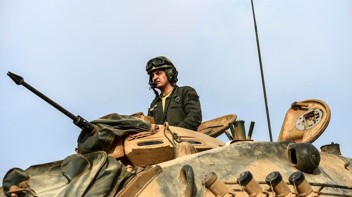 This picture taken around 5 kilometres west from the Turkish Syrian border city of Karkamis in the southern region of Gaziantep, on August 25, 2016 shows a soldier looking on as Turkish Army tanks drive to the Syrian Turkish border town of Jarabulus. (AFP)