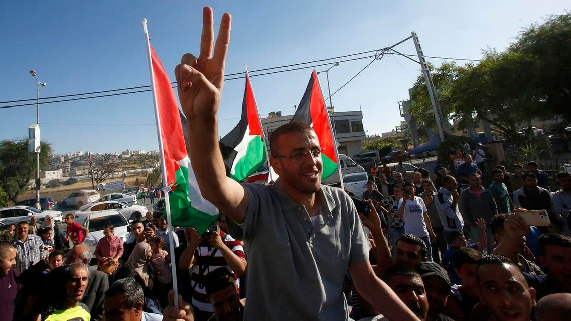 """Palestinian journalist Mohammed al-Qiq, who was held by Israel without trial and went on hunger strike for more than three months, flashes the """"V"""" for victory sign as he arrives in the village of Dura near Hebron, in the occupied West Bank, following his release from the Israeli Nafha prison on May 19, 2016. (AFP)"""
