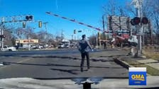 WATCH: Man jumps out of car to save woman from oncoming train