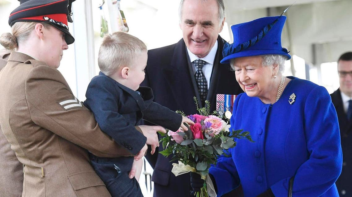 Two-year-old Alfie Lun, 2, is held up by his mother Michelle Lun as he hands a bouquet to Britain's Queen Elizabeth during the the unveiling of a national memorial honouring the Armed Forces and civilians who served their country during the Gulf War and conflicts in Iraq and Afghanistan in London Thursday March 9, 2017. (AP)