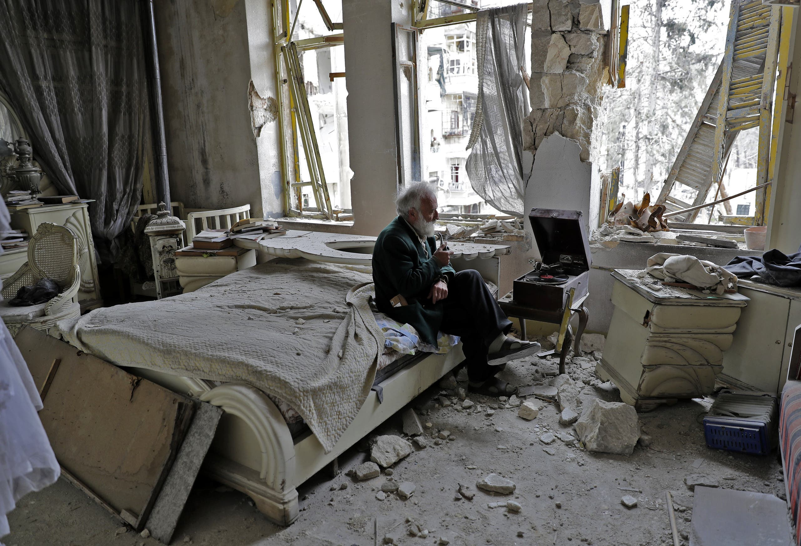 Mohammad Mohiedine Anis, 70, smokes his pipe as he sits in his destroyed bedroom listening to music on his vinyl player in Aleppo's formerly rebel-held al-Shaar neighbourhood. AFP