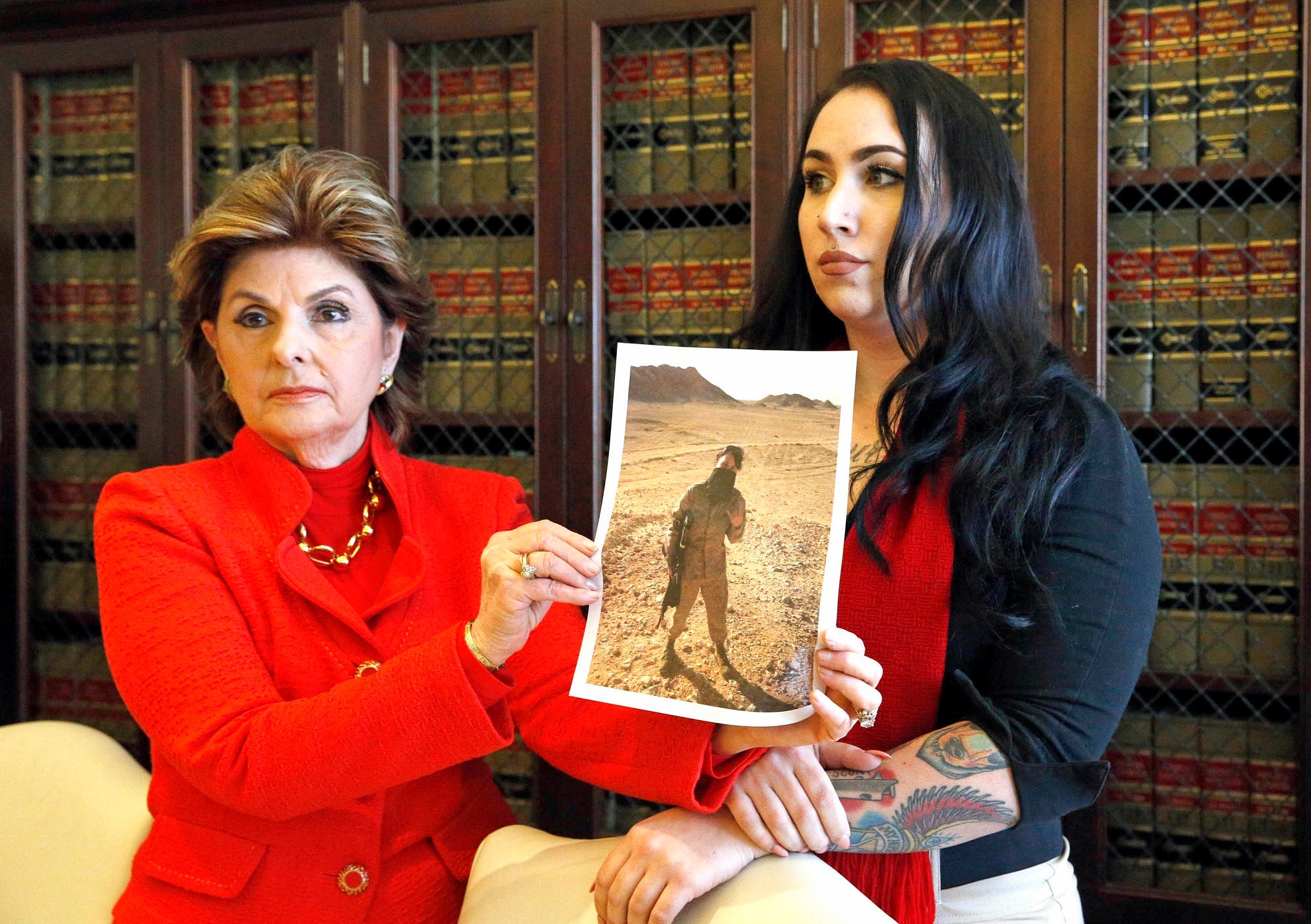 Former Marine Erika Butner, right, and attorney Gloria Allred hold photos of Butner in uniform, as she and another active-duty female Marine said photographs of them were secretly posted online without their consent. (AP)