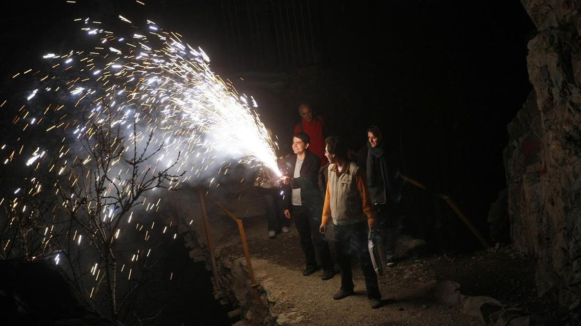"""An Iranian man holds a firecracker during the """"Chaharshanbeh Soori"""" or (Festival of Fire) in Darakeh mountain north of Tehran, late March 18, 2008. (AFP)"""