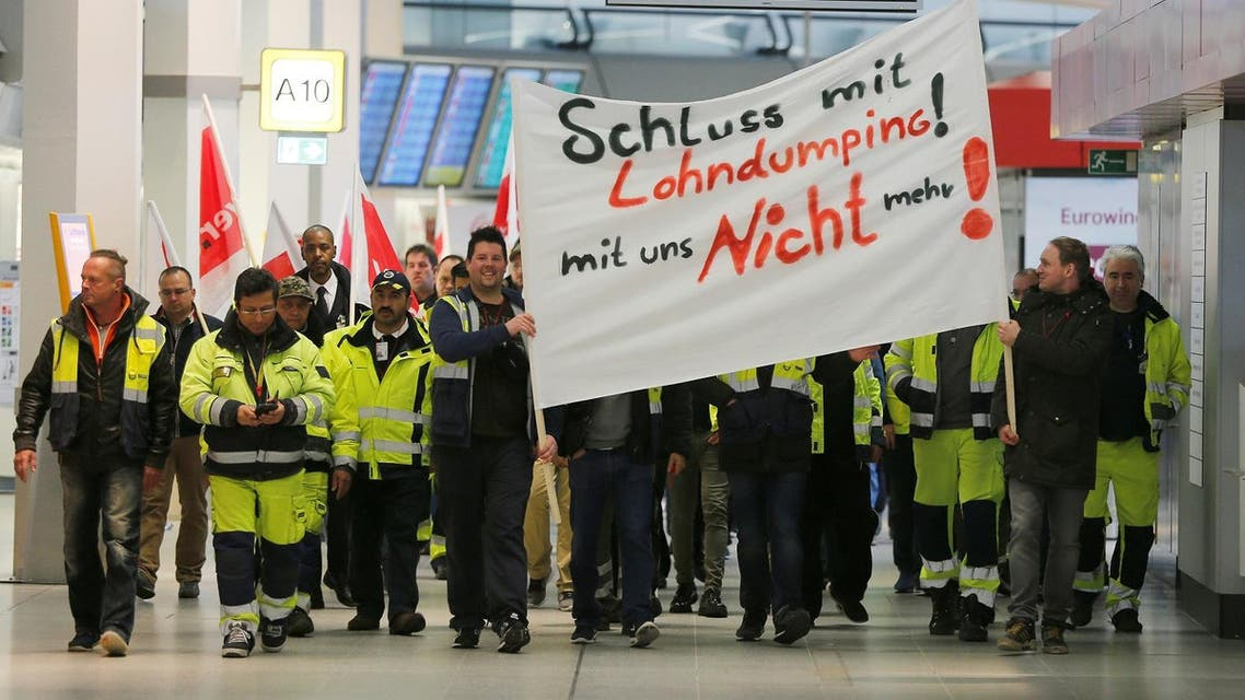 Members of Germany's Verdi union take part in a warning strike by ground services, security inspection and check-in staff at Tegel airport in Berlin, on March 10, 2017. (Reuters)