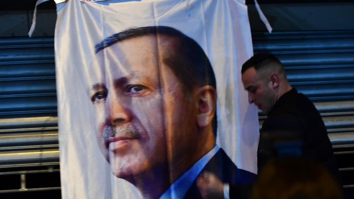 A man gestures in front of a flag bearing a portrait of Turkish President Recep Tayyip Erdogan as Turkish residents of the Netherlands gather for a protest outside Turkey's consulate in Rotterdam on March 11, 2017. Protests erupted in the Dutch port city of Rotterdam late on March 11 outside the Turkish consulate amid a row with Ankara after Dutch authorities banned the visits of Turkish ministers. About 1,000 people waving Turkish flags gathered on the street leading to the consulate, as tensions rocketed over rallies abroad to help Ankara gain backing for an April referendum vote. AFP