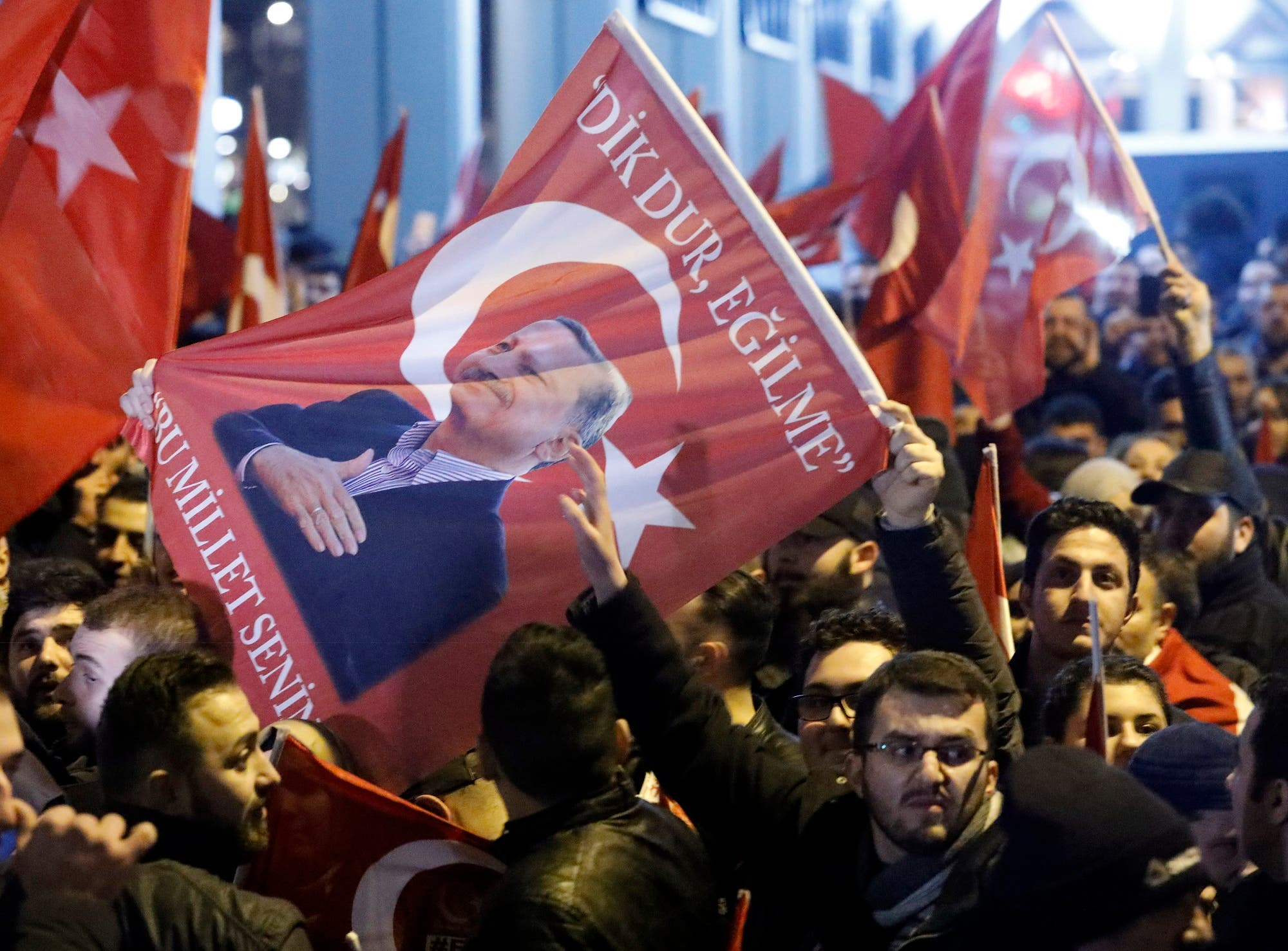 Demonstrators with banners of Turkish President Recep Tayyip Erdogan gather outsidethe Turkish consulate to welcome the Turkish Family Minister Fatma Betul Sayan Kaya. (Reuters)