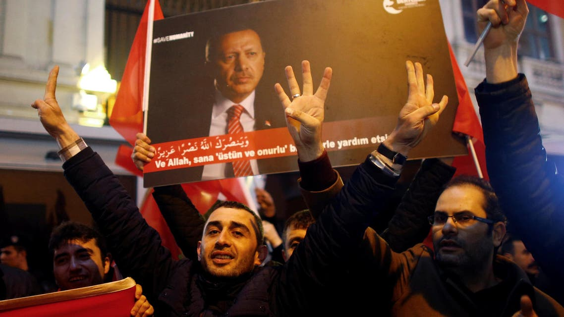 People, holding a banner with a picture of Turkish President Tayyip Erdogan, shout slogans during a protest in front of the Dutch Consulate in Istanbul, Turkey, early March 12, 2017