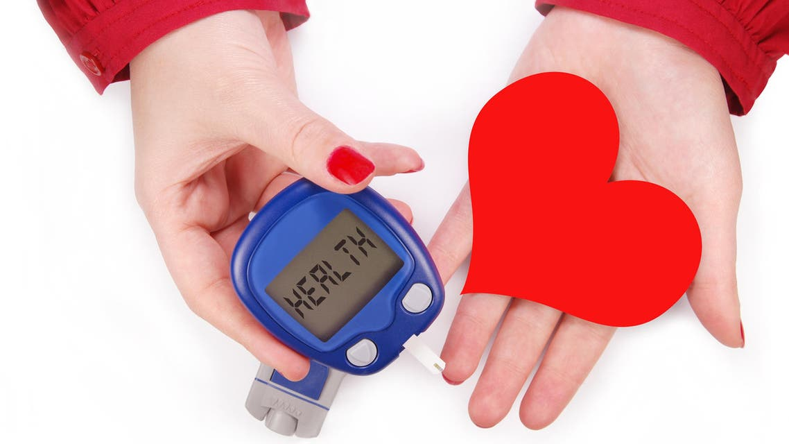 Two female hands holding a blood testing machine and heart