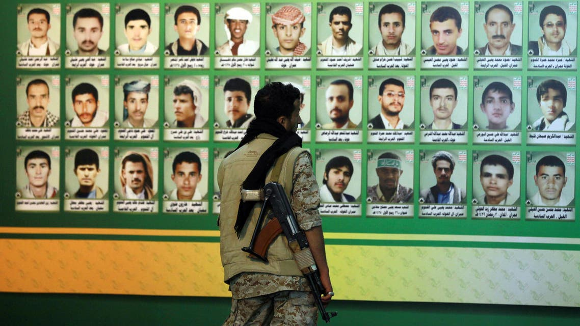 """A Huthi militiaman looks at a wall bearing the portraits of """"martyrs"""", who were reportedly killed during the six-year conflict in the northern Yemeni province of Saada between the Shiite Muslim movement and government forces, during a memorial event in the capital Sanaa on March 5, 2015"""