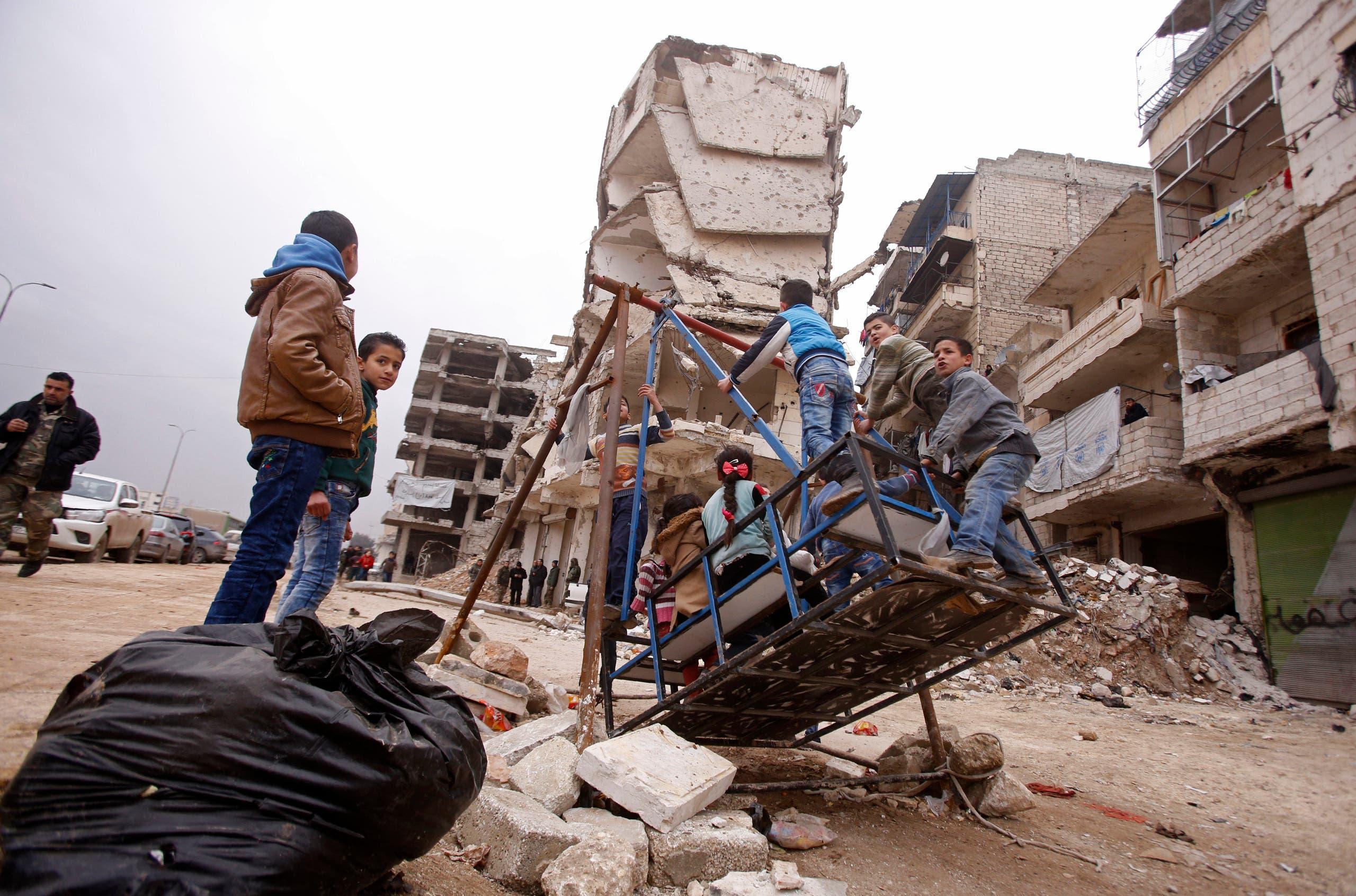 أطفال سوريون يلعبون قرب الدمار في حلب في ديسمبر 2016