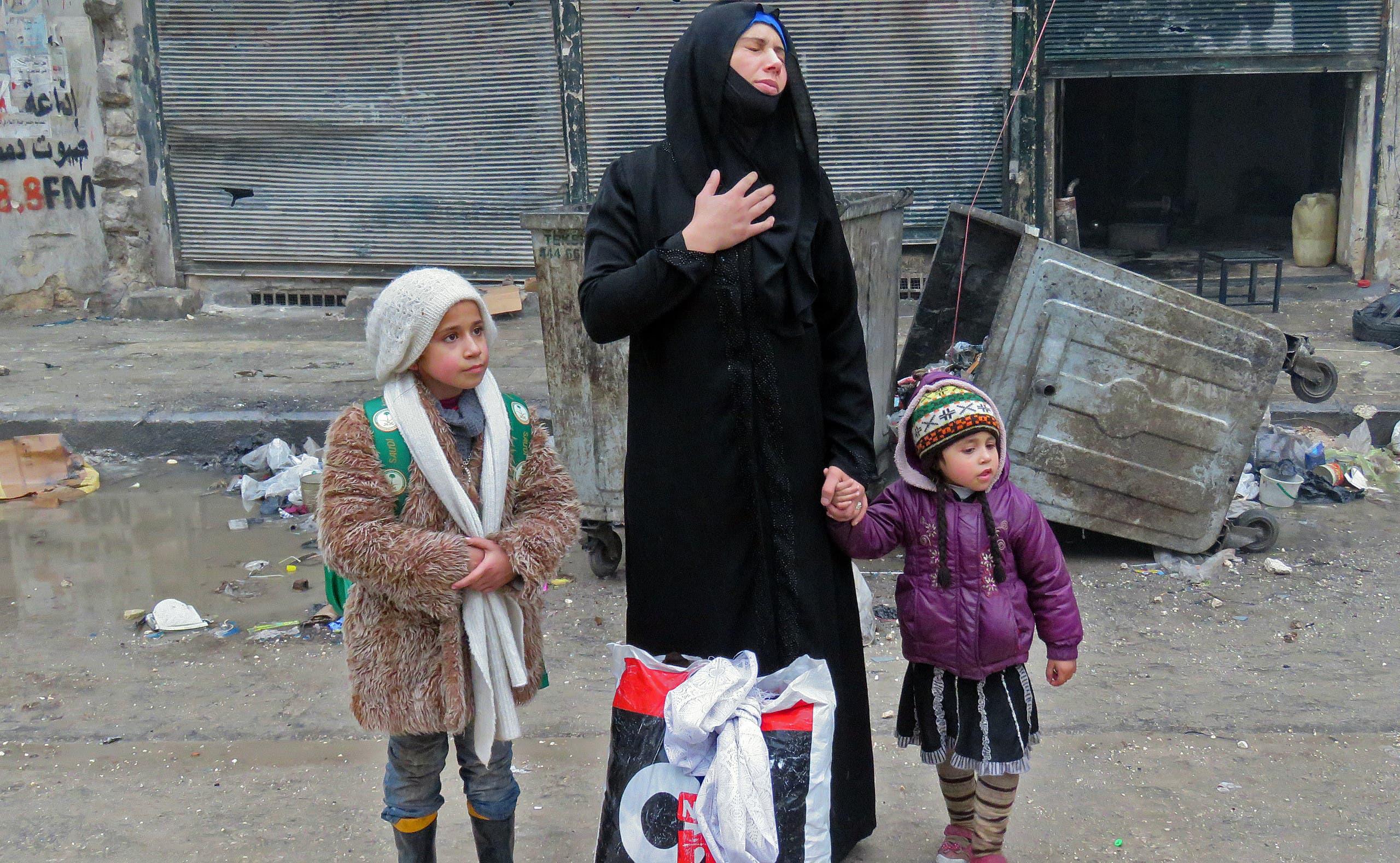امرأة سورية تهرب مع ولدين من العنف في حلب بعد اقتحام النظام لآخر معاقل المعارضة في المدينة بـ2016