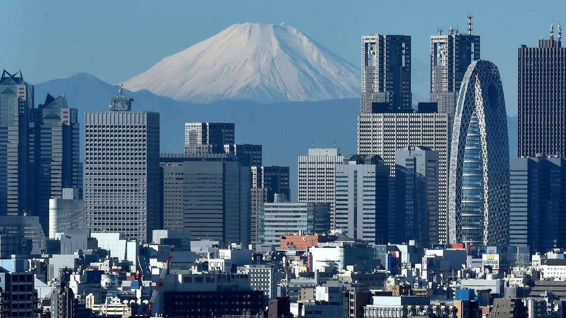 Japan's highest mountain, Mount Fuji (C) is seen behind the skyline of the Shinjuku area of Tokyo on December 6, 2014. Tokyo stocks closed at a seven-year high on December 5 -- extending their winning streak for a sixth straight day -- as a falling yen and oil prices continue to boost investor spirit. AFP