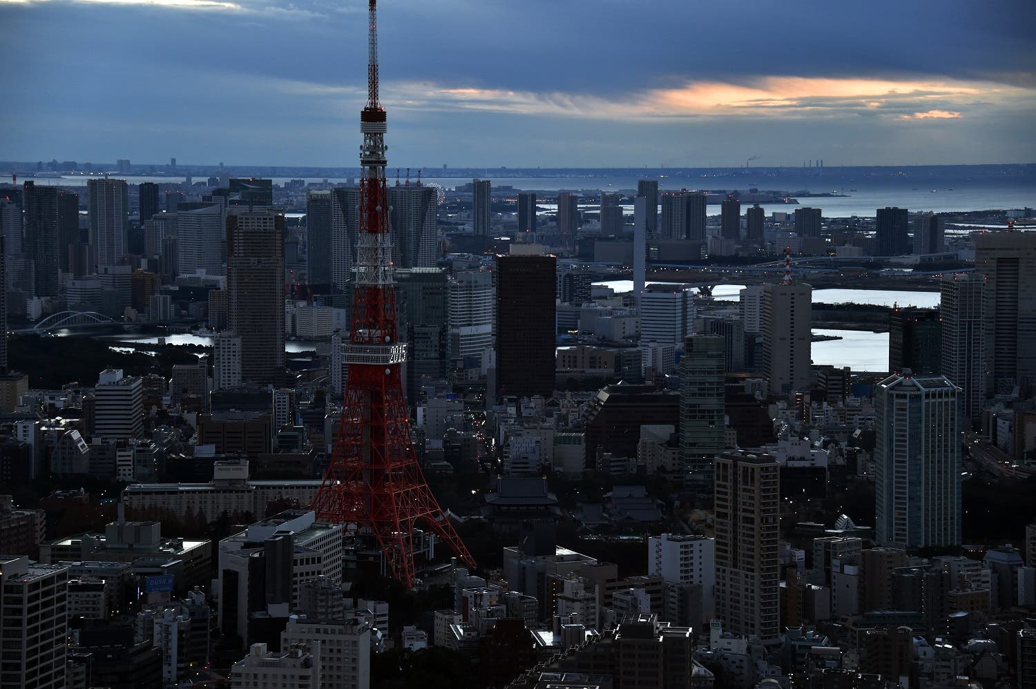 Clouds obscure the sun rise as people come out to see dawn bring in the new year over Tokyo Tower (L) and the city's skyline on New Year's Day on January 1, 2015. Millions of Japanese people visit shrines and temples to pray for the well-being of their families at the New Year. AFP