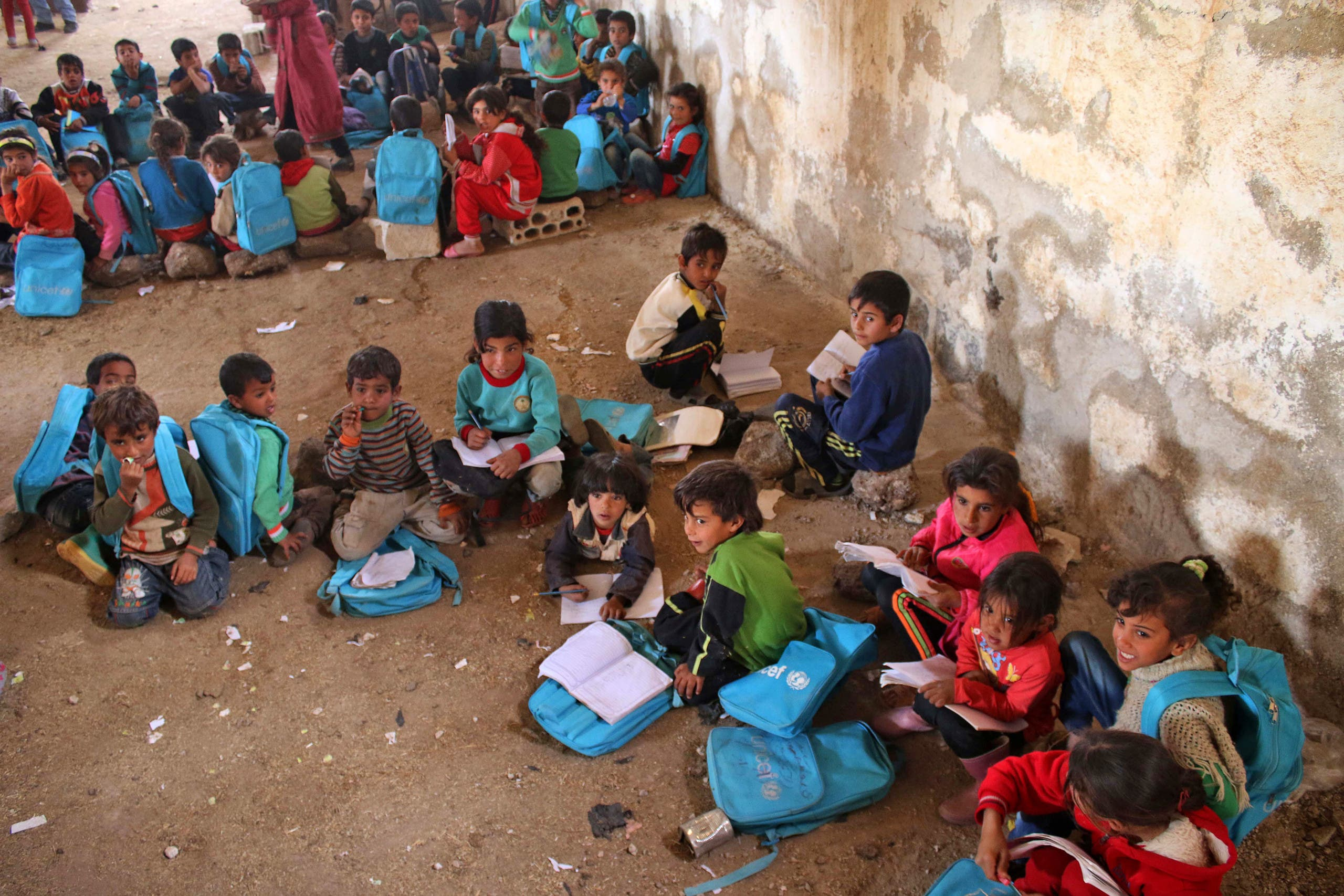 Syrian children sit during class a barn that has been converted into a makeshift school to teach internally displaced children from areas under government control, in a rebel-held area of Daraa, in southern Syria on November 10, 2016