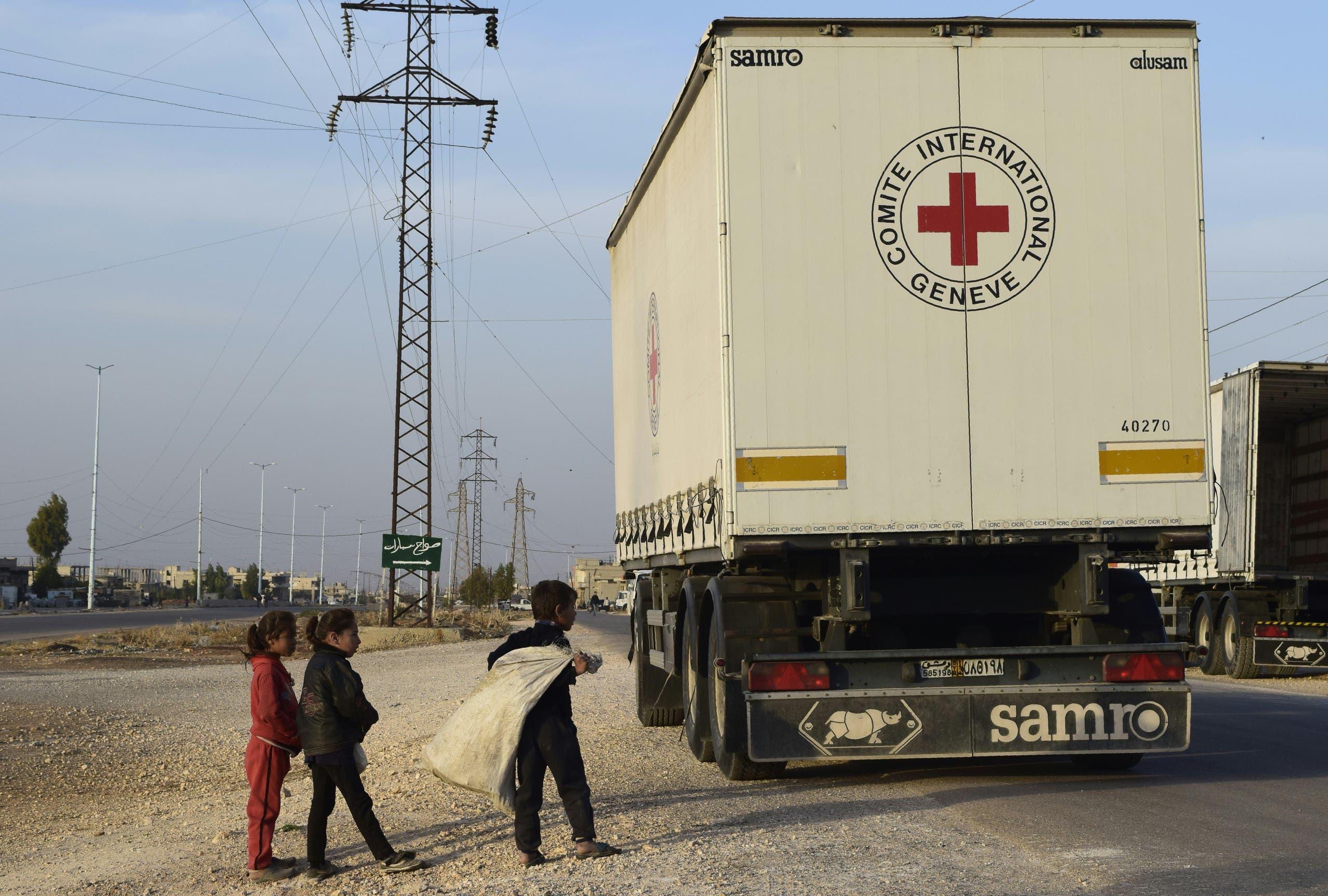 أطفال سوريون يتجمعون قرب قافلة مساعدات في حمص في نوفمبر 2011