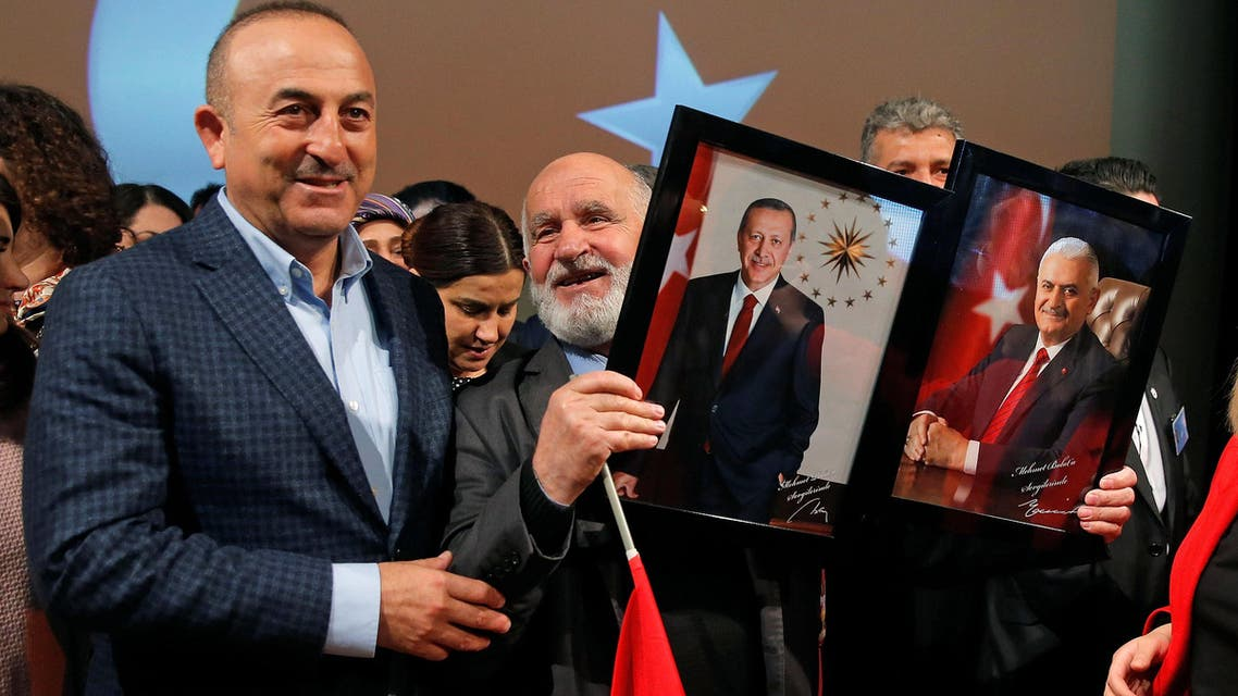 Turkish Foreign Minister Mevlut Cavusoglu poses with a supporter holding portraits of Turkish President Recep Tayyip Erdogan and Prime Minister Binali Yildirim (R) at the end of a political rally on Turkey's upcoming referendum, in Metz, France, March 12, 2017